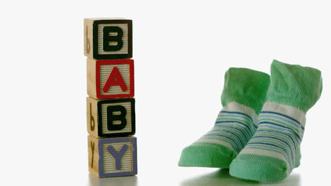 Green slippers falling besides baby blocks Live Action