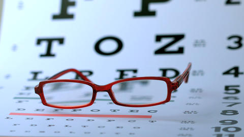 Red glasses falling on eye test Footage