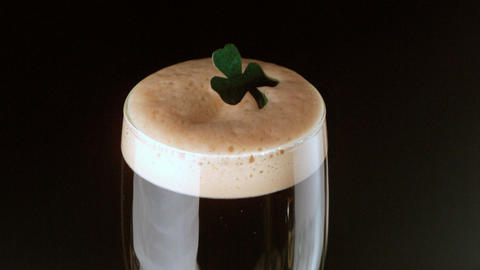 Shamrock landing on head of pint of stout Filmmaterial