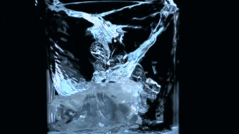Two ice cubes falling into glass on black backgrou Footage