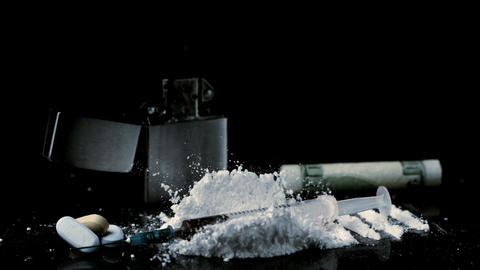 Syringe falling on pile of white drug with syringe Footage