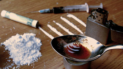 Drug cooking on a spoon surrounded by pile lines a Footage