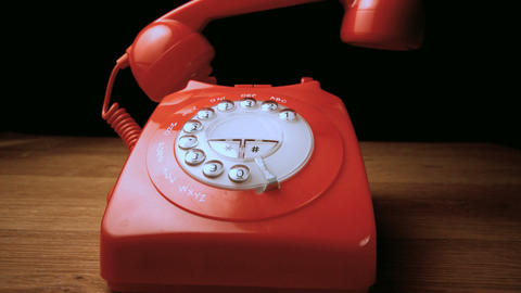 Red receiver falling onto retro dial phone Footage