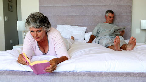 Mature couple reading in the bedroom Footage