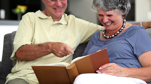Mature couple laughing while looking at a book Footage