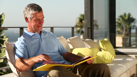 Mature man looking at picture album on the balcony Footage