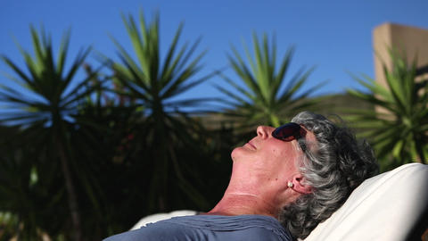 Mature woman sunbathing in a deckchair Footage