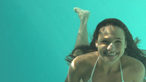 Smiling woman swimming underwater Footage