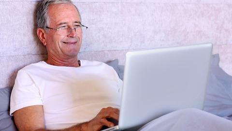 Elderly man using laptop in bed Footage