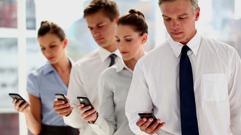 Business people standing in line with their smartp Footage