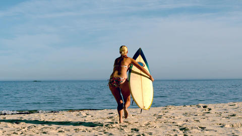 Blonde surfer picking up board and running towards Footage