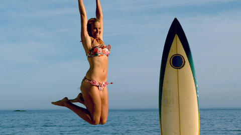 Blonde woman jumping beside her surfboard Footage