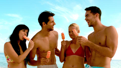 Friends laughing and eating ice cream on the beach Footage