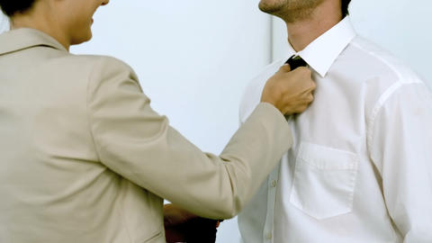Businesswoman helping a man tying his tie Live Action
