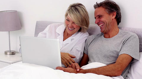 Mature couple using laptop in the bed Footage