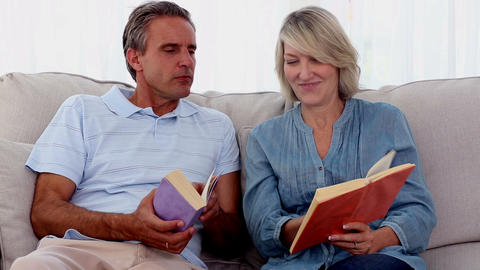 Mature people reading books on the couch Footage