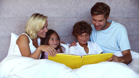 Parents reading a funny story to their children Footage