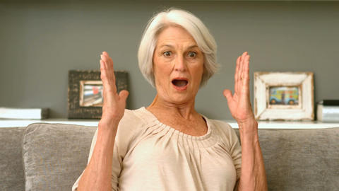 Retired Woman Looking Shocked On Couch stock footage
