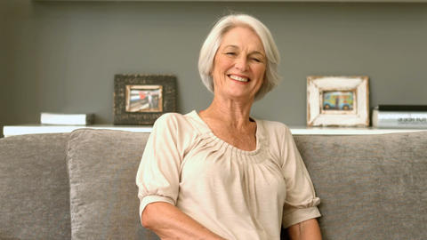 Happy Retired Woman Smiling On Couch stock footage