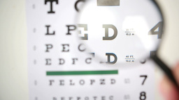 Magnifying glass scanning over eye test Footage