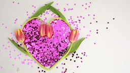 Light shining over heart made of pink confetti framed by tulips Footage