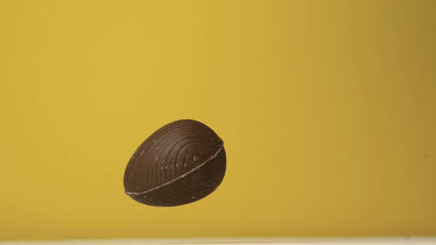 Chocolate easter egg falling against yellow backgr Footage