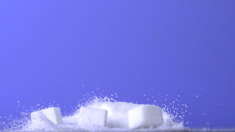 Sugar cubes falling down into pile of sugar on purple background Live Action