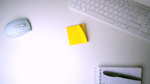 Yellow post it falling on office desk Live Action