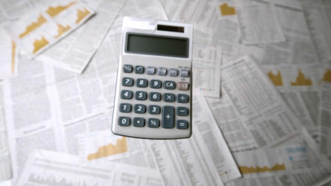 Pocket calculator falling and bouncing on papers Footage