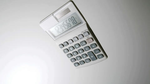Pocket calculator falling on white surface Footage