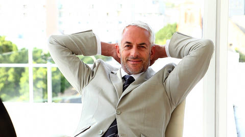 Confident businessman relaxing on his chair Live Action