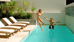 Siblings diving into the swimmingpool Footage