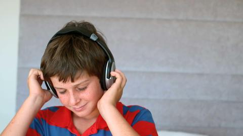 Dancing young boy enjoying music with headphones Footage