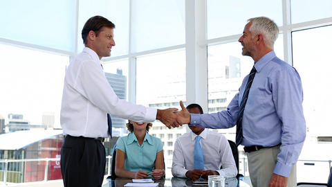 Businessmen shaking hands in the meeting room Footage