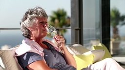Mature woman enjoying glass of wine on balcony Footage