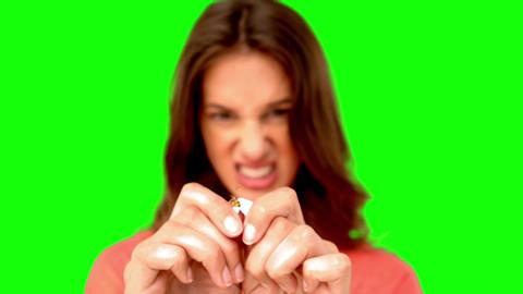 Woman breaking a cigarette on green screen Footage