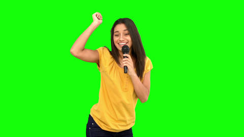 Woman singing and dancing on green screen Footage