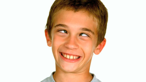 Little boy squinting against white background Footage