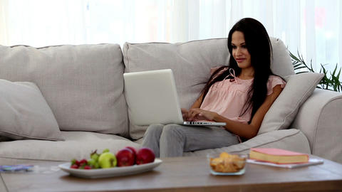 Attractive woman using laptop on the couch Footage