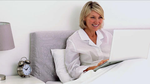 Mature woman using laptop in her bedroom Footage