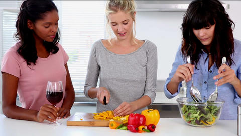 Attractive friends preparing salad in the kitchen Footage