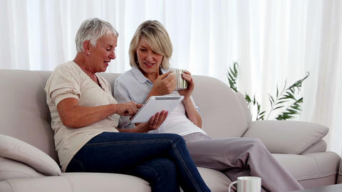 Mature women using tablet pc on the couch Footage