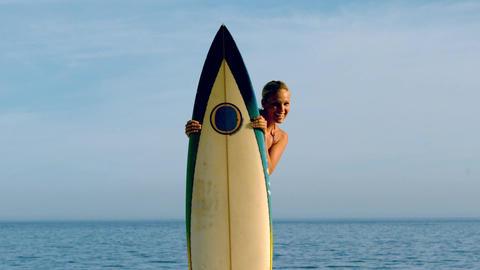 Female surfer peeking from behind her board Footage