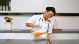 Home nurse pouring orange juice in kitchen Footage