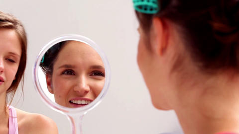 Girl wearing rollers looking in mirror and talking Footage