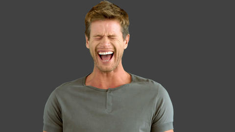 Handsome man laughing on grey screen Footage