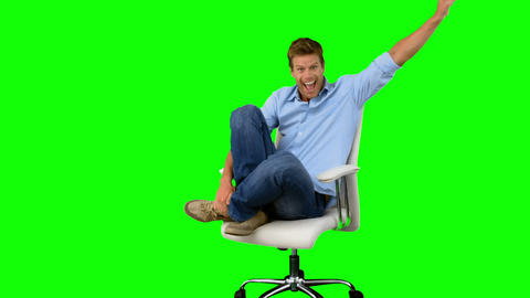 Smiling man cheering and turning on swivel chair o Footage