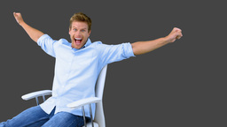 Man on swivel chair raising arms to show his success on grey screen Live Action