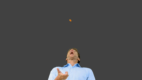 Man catching an orange segment with his mouth on g Footage