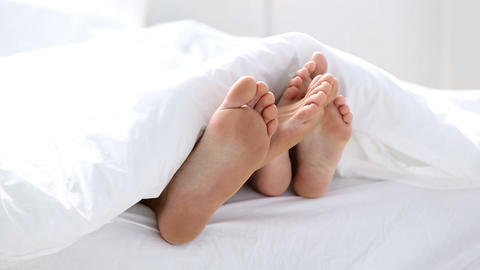 Pair of feet playing footsie under the covers Footage